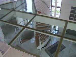 Privatkunde - Spindeltreppe mit Anschluss an den Verbindungssteg der Galerie, Stegbelag aus begehbarem Glas